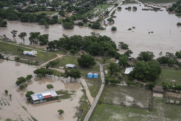 In this aerial photo a barn with a Texas flag painted on its roof is surrounded by water near Martindale, Texas, after the San Marcos River flooded, Sunday, May 24, 2015. Record rainfall was wreaking havoc across a swath of the U.S. Midwest on Sunday, causing flash floods in normally dry riverbeds, spawning tornadoes and forcing at least 2,000 people to flee. (Rodolfo Gonzalez/Austin American-Statesman via AP)  AUSTIN CHRONICLE OUT, COMMUNITY IMPACT OUT, INTERNET AND TV MUST CREDIT PHOTOGRAPHER AND STATESMAN.COM, MAGS OUT