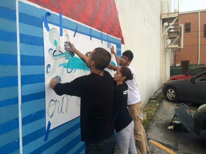 "From left: Esteban Valdez, CDCB employee Cynthia Rocha and Josué spray ""Home is where our story begins"" onto the mural."